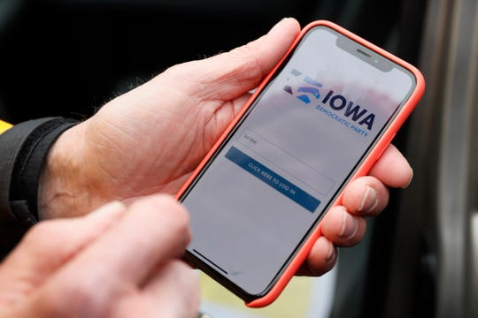 Precinct captain Carl Voss, of Des Moines, Iowa, holds his iPhone that shows the Iowa Democratic Party's caucus reporting app Tuesday, Feb. 4, 2020, in Des Moines, Iowa.