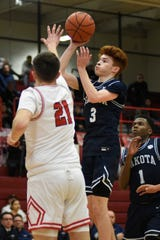 Macomb Dakota guard Joey Tocco, right, puts up a shot past the reach of Roseville boys basketball player Anthony Rosati in the fourth quarter.