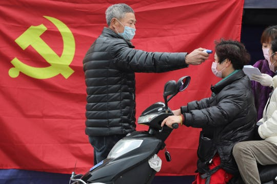 A volunteer stands in front of a Communist Party flag as he takes the temperature of a scooter driver at a roadside checkpoint in Hangzhou in eastern China's Zhejiang Province, Monday, Feb. 3, 2020.