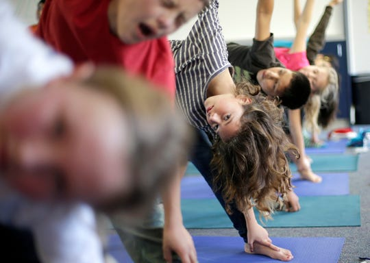 Students hold their position during a yoga class at Capri Elementary School in Encinitas, Calif.
