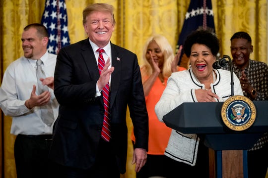President Donald Trump reacts as Alice Johnson, an inmate whose life sentence was commuted thanks in part to the efforts of Kim Kardashian West, right, thanks the media while speaking at the 2019 Prison Reform Summit and First Step Act Celebration in the East Room of the White House in Washington, Monday, April 1, 2019.