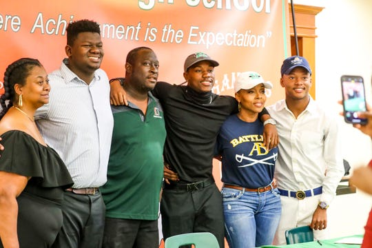 Cameron James, Coach Sammy Brown, Jarvis Jones, and Zavion Balle, and a few of their moms get a photo after signing. Dunbar held its National Signing Day ceremony for four football players -- Albert Nunes (Hutchinson Community College), Jarvis Jones (Marshall), Cameron James (ASA Miami), and Zavion Battle (Alderson Broaddus).