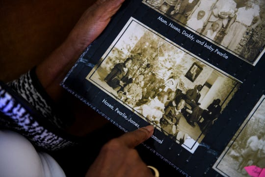 Pearlie Harris points to a photograph of herself as a baby with her family while looking through a photo album in her home Monday, Jan. 6, 2020.
