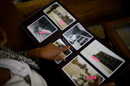 Pearlie Harris points to a high school graduation photo of herself while looking through a photo album in her home Monday, Jan. 6, 2020.
