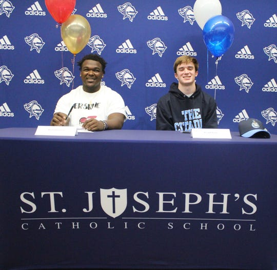 St. Joseph's Catholic School's Rashad Luckey (left) and Joseph Poole are recognized during a ceremony for students who will play sports in college Wednesday.