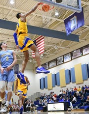 Wren junior Bryce McGowens(5) dunks near D.W. Daniel senior Bubba Mcatee during the third quarter at D.W. Daniel High School in Central on Tuesday.