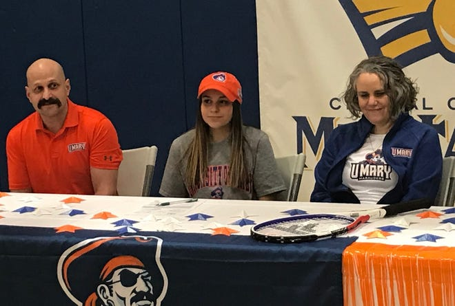 Great Falls Central senior Sam Purpura, flanked by her father Jason and mother Lori, prepares to sign a college letter-of-intent to play tennis at the University of Mary in Bismarck, N.D. next fall.
