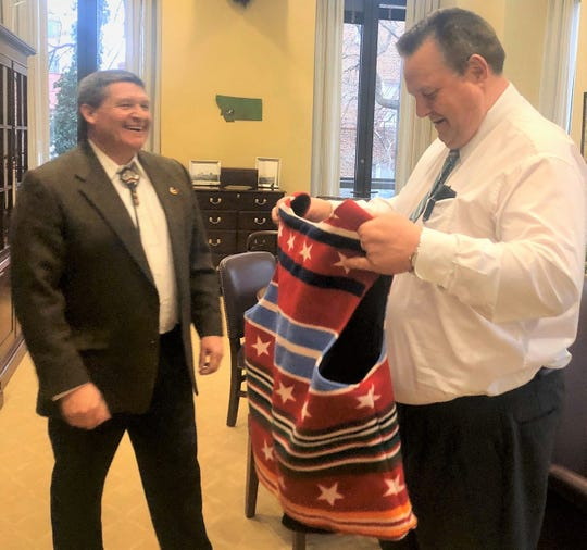 Gerald Gray, left, chair of the Little Shell Tribe of Chippewa Indians of Montana, gives Sen. Jon Tester a vest on Tuesday for Tester's help in getting federal recognition for the tribe. Gray attended President Donald Trump's State of the Union address as Tester's guest later in the day.