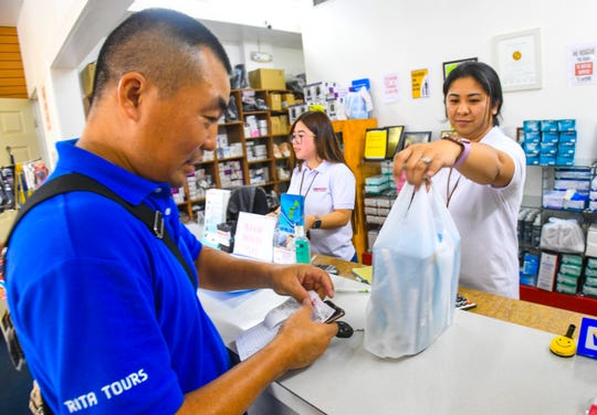 """Medquest Medical Supply employee Angelica Fontillas hands four boxes of medical face masks purchased by customer, Mark Xia, at the Tamuning store on Wednesday, Feb. 5, 2020. """"I scare,"""" explained Xia, after he bought the masks, primarily for use by his eight-year-old daughter, in light of the threat of the coronavirus. Fontillas estimated the store normally sells less than one hundred boxes of the masks over a one week period. She and other staff members estimate that since Thursday last week, the store has sold over 3,000 boxes."""