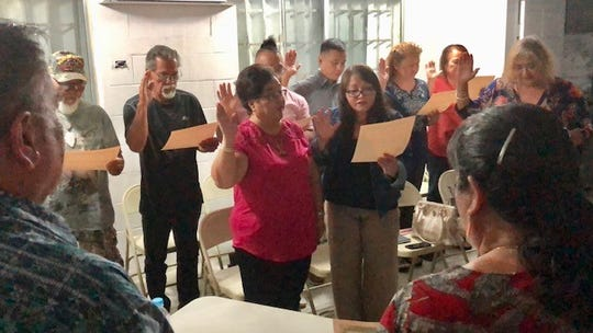Mayors' Council of Guam President and Dededo Mayor Melissa Savares, right, foreground, administers the oath of office to the 10 members of the Yona Municipal Planning Council on Wednesday night, Feb. 5, 2020.