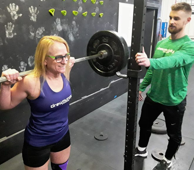Linda K. Smith, 55, of Iowa City is making a national name for herself in her age group in powerlifting. Here she warms up with some squats under supervision of her coach Drew Murphy at his Tiffin gym.