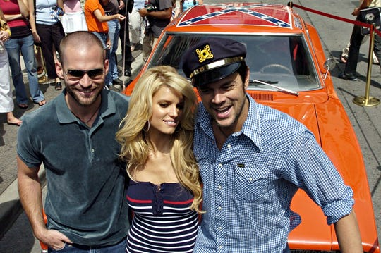 """Actors Seann William Scott, left, Jessica Simpson, center, and Johnny Knoxville pose in front of the car """"The General Lee"""" following a press conference for the film """"The Dukes of Hazzard"""" in a Toronto photo from Aug. 1, 2005. Knoxville and Scott, who play Luke and Bo Duke in """"The Dukes of Hazzard,"""" didn't exactly perfect the art of """"yee-haw"""" for the film."""