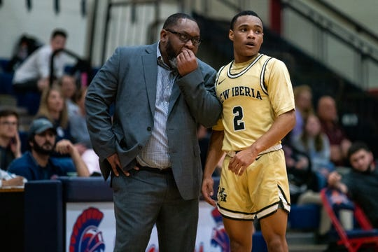 New Iberia head coach Todd Russ speaks to Stiles Jolivet on the sidelines as the Comeaux High Spartans beat the New Iberia Yellow Jackets, 59-57, in double-overtime on Tuesday, Feb. 4, 2020.