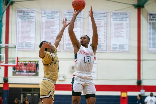 Comeaux High's Tre Harris shoots over a defender during the play  as the Comeaux High Spartans beat the New Iberia Yellow Jackets, 59-57, in double-overtime on Tuesday, Feb. 4, 2020.