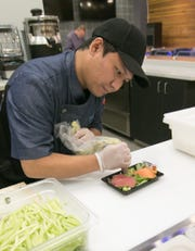 Hissho Sushi & Craft Beer Bar franchisee Gan Hpung prepares a sweet roll sashimi at the new store inside the Brighton Meijer on Wednesday, Feb. 5, 2020.