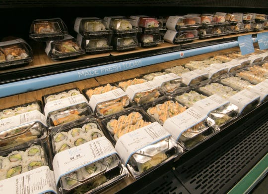 Customers can select from boxes of sushi products in the front counter of Hissho Sushi & Craft Beer Bar inside the Brighton Meijer, shown Wednesday, Feb. 5, 2020.