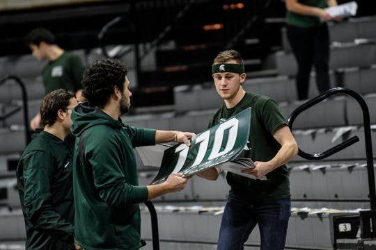 Workers remove signs celebrating Mark Dantonio's career wins from the Izzone before Michigan State's game against Penn State on Tuesday, Feb. 4, 2020, at the Breslin Center in East Lansing.