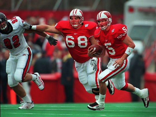Quarterback Brooks Bollinger scrambles for yardage with the help of Mark Tauscher (68) against Indiana on October 16, 1999 at Camp Randall in Madison. The badgers beat Indiana, 52-0 .