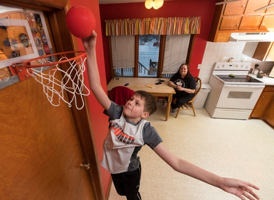 Dawson Bornheimer, 11, plays basketball in the kitchen at his home in Edgar as his mother, Melissa, watches. When Dawson was an infant, he tested positive for severe combined immunodeficiency and was cured with a transplant of umbilical cord blood, which is similar to a bone marrow transplant.