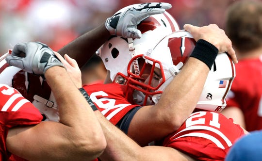 Badgers swarm Chris Maragos at the end of the game Sept. 13, 2009, after Maragos made the interception in the second overtime that allowed the Badgers to kick the winning field goal in a 34-31 win over Fresno State.