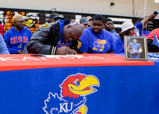"""Oak Grove's Kenan Caldwell signs his letter of intent with Kansas University on National Signing Day at the Oak Grove High gym on Feb. 5. """"Man, it feels great,"""" Caldwell said. """"I'm the first guy to sign to a qualifying school from Oak Grove in 25 years. It's a blessing"""""""