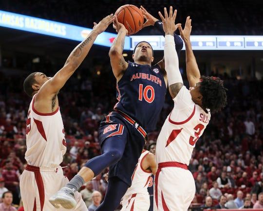 Auburn guard Samir Doughty (10) drives to the basket against Arkansas' Reggie Chaney (35) and Desi Sills (3) at Bud Walton Arena on Feb. 4, 2020.
