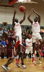 Lee's De'Marquiese Miles (15) and Lee's Jamal Albritton (22) go up for a rebound during the first half.
