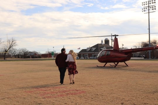 Koby Younce of Murfreesboro and his girlfriend, Kaylee Belanger, walk to the helicopter he chartered to take her from Todd County Central High School, where she teaches biology, to propose to her on a secluded farm in Smyrna.