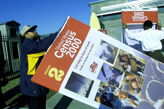 Jerome Cannon, left, from Chattanooga and Ed Bryant from Memphis, who are traveling with the United States Census 2000 road tour, set up giant posters at the census site at the farmers market Feb. 20, 2000.