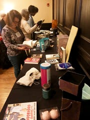 Nashville Women's Breakfast Club members browse the table of swappables at the Ms. Cheap Swap-a-thon.