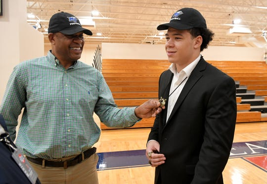 Rodney Curtis, left, celebrates with his son, Brentwood Academy linebacker Devyn Curtis, who is headed to play football at MTSU, during a signing day celebration Wednesday.