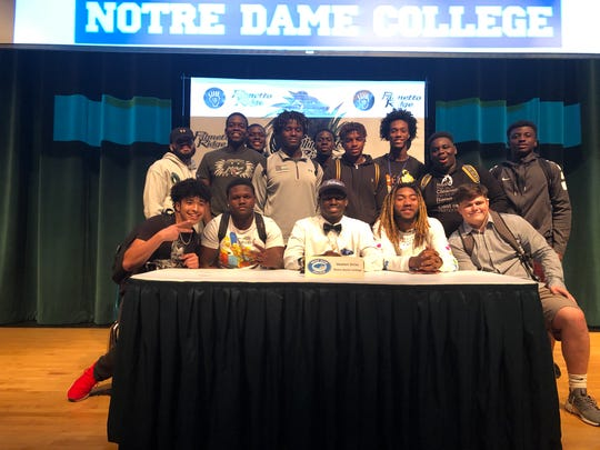 Palmetto Ridge football player Voshon Siriac poses with teammates after signing a national letter of intent with Notre Dame College, a Division II school in Ohio, during a ceremony on Wednesday, Feb. 5, 2020.