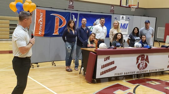 First Baptist Academy athletic director Billy Sparacio congratulates the Lions athletes who committed on National Signing Day, Wednesday, Feb. 5, 2020. Seated at the table (L to R): beach volleyball player Jordan Benoit (Pepperdine), soccer player Malaya Melancon (FGCU), lacrosse player Megan Williams (Lincoln Memorial).