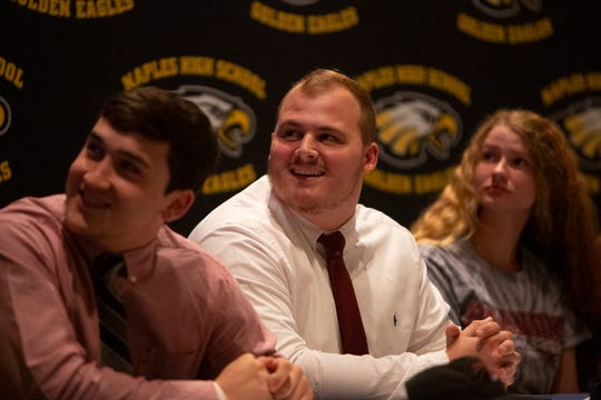 CJ Dietzel, left, Mike Fangman and Kyleigh Chickering watch a highlight reel featuring CJ Dietzel during a National Signing Day ceremony, Wednesday, Feb. 5, 2020, at Naples High School.