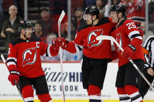 New Jersey Devils defensemen Andy Greene (6) and Mirco Mueller (25) congregate around left wing Miles Wood, center, after Wood scored during the first period of the team's NHL hockey game against the Montreal Canadiens, Tuesday, Feb. 4, 2020, in Newark, N.J.