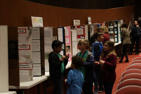A student at last year's Science and Engineering Fair explains his project to peers.