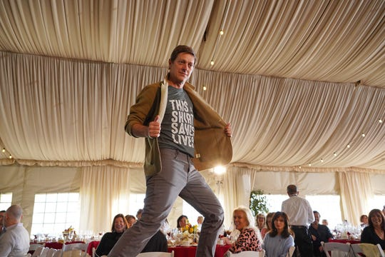 Actor Kevin Rahm struts his stuff — and his life-saving T-shirt — at the Catwalk celebrity fashion show.