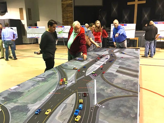 Members of the public look at a diverging diamond interchange overlaid onto Pine Forest Road and Interstate 10 at a public workshop on Tuesday, Feb. 4, 2020.