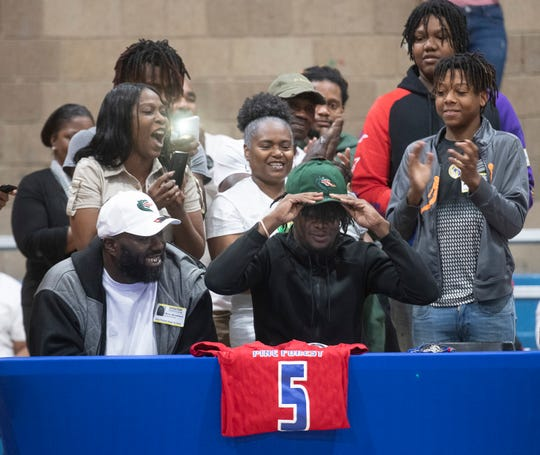 Family and friends surround Dacarrion McWilliams as he announces his plans to attend the University of Alabama Birmingham during a National Signing Day event at Pine Forest High School on Wednesday, Feb. 5, 2020.