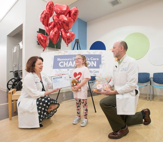 """Madi Baxley, 10, is presented with the first-ever Nemours Children's Care Champion Award at Nemours Children's Specialty Care in Pensacola. Baxley, who has a rare chromosomal disorder called Turner Syndrome, created a """"cheer chest"""" three years ago and regularly donates toys and knick-knacks for fellow cardiology patients."""