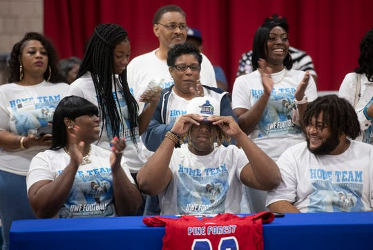 Family and friends surround Thomarius Walker as he announces his plans to attend the University of West Florida during a National Signing Day event at Pine Forest High School on Wednesday, Feb. 5, 2020