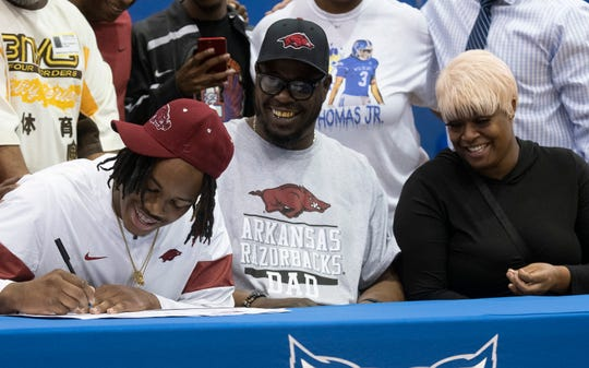 Family and friends surround Eric Thomas, Jr., as he announces his plans to attend the University of Arkansas during a National Signing Day event at Washington High School on Wednesday, Feb. 5, 2020.