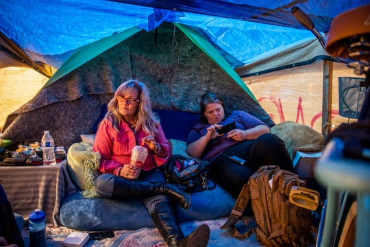 Darlene Carchedi, left, and Letha Burns discuss the coming cleanup in Carchedi's home at an encampment of around 400 people near Central Arizona Shelter Services and other services in Phoenix on Tuesday, Feb. 4, 2020.