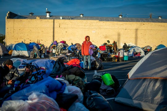 People temporarily set up their tents in a parking lot during a cleanup of an encampment of around 400 people near the Human Services Campus in Phoenix on Feb. 5, 2020.