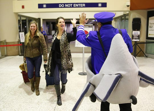 """Sky Harbor Airport mascot """"Chuck"""" greets Bernadette Messmore who was on the last flight to ever arrive at Terminal 2 on Feb. 4, 2020. The terminal will close after today. At left is her daughter, Lauren."""