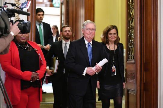 Mitch McConnell, líder de la mayoría republicana en el senado, camina muy sonriente tras emitirse el voto del juicio político.