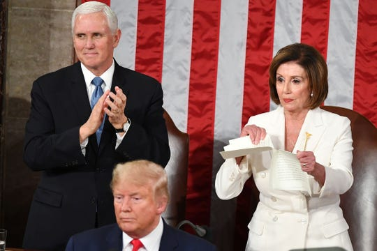 House Speaker Nancy Pelosi rips a copy of President Donald Trump's speech as she stands behind him.