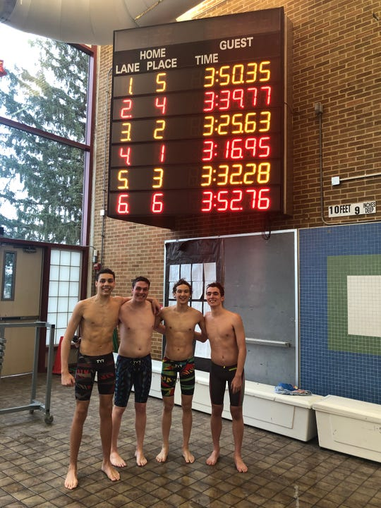 Members of the Wappingers 400 freestyle relay team pose in front of the board on Feb. 1 after their 3:16.95 time qualified for the state championships. From left: Sebastian Smith, Kyle McGregor, Steve Holan and Matthew McGregor.