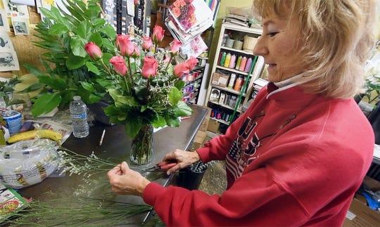 Karen Hinson creates a rose vase at Stagemyer Flower Shop in North York.