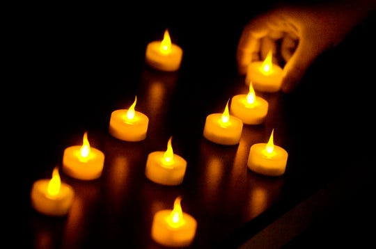 A file photo of someone placing candles on a table during a vigil.